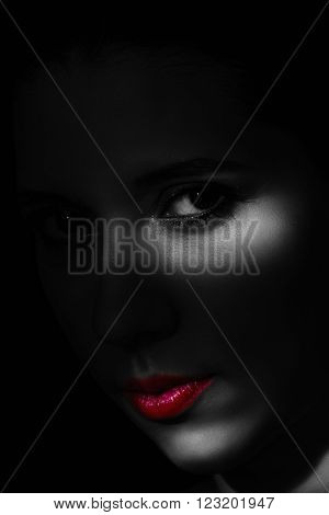 Artistic beauty portrait of young woman with creative lighting effect. Fashion close up black and white photo of girl face with red lips.