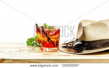 Red tropical drink. Campari aperol caipirinha sangria. Holidays concept with sunglasses and straw hat