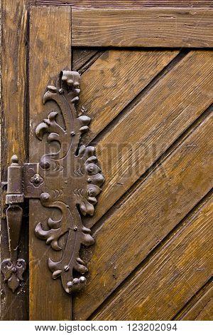 Vintage iron door hinges. Wrought iron hinges on the wooden door.