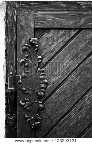 Vintage iron door hinges. Wrought iron hinges on the wooden door.