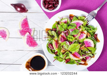 Red beans watermelon radish lettuce leaves walnuts salad close-up