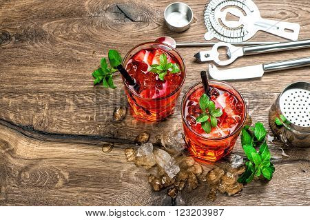 Red drink with ice mint leaves and strawberry. Cocktail making bar tools