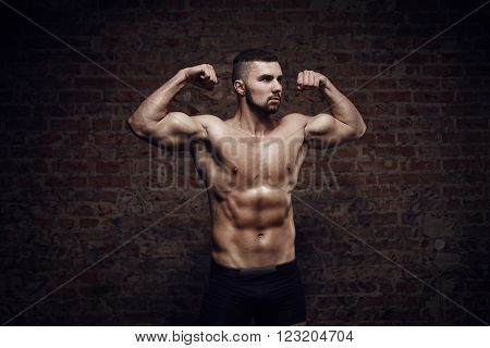 Young muscular man showing double biceps near red brick wall