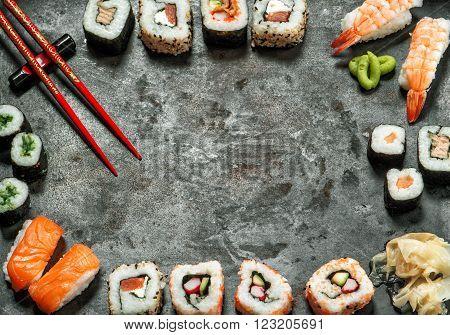 Sushi rolls maki nigiri salmon shrimp tuna tofu rice avocado wasabi pickled ginger. Traditional japanese food background