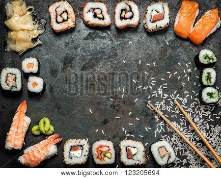 Sushi rolls maki nigiri salmon wasabi shrimp tuna tofu rice avocado pickled ginger. Asian food background. Dark toned picture