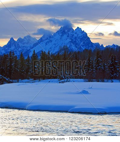 Snake River flowing past snowbanks below the Grand Tetons Mountain Range in Grand Teton National Park in Wyoming USA
