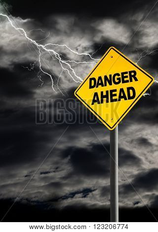 Danger Ahead sign against a dark cloudy and thunderous sky. Conceptually warning of danger ahead. Copy space and vertical orientation.