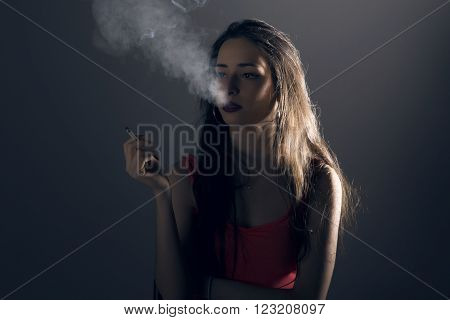 Beautiful young woman with a cigarrette, exhaling smoke, over grey background.