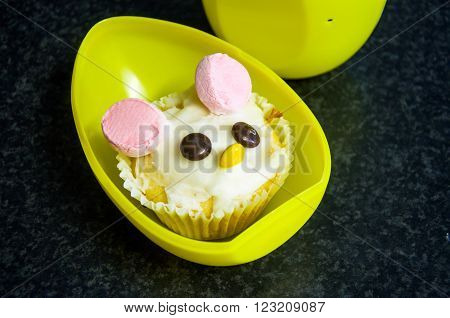 Frosted and decorated Easter bunny cupcake with chocolate candy eyes and nose, pink marshmallow ears set in a yellow plastic Easter egg.