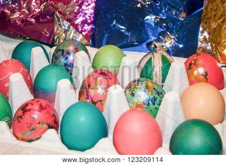Egg carton with colourfully dyed Easter eggs with metallic accents and a metallic paper background.