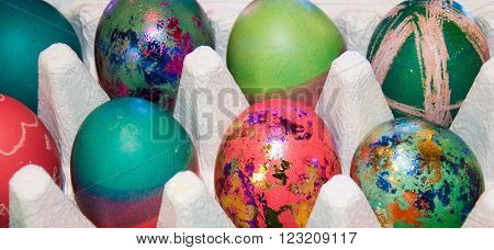 Egg carton with organic brown eggs and colourfully dyed Easter eggs.