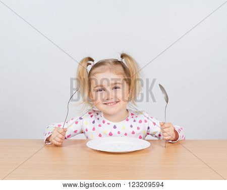 Little girl holding fork and spoon with empty plate ready for food.