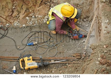 MALACCA, MALAYSIA -OCTOBER 20, 2016: Construction workers make holes at the building pile cap using mobile drilling machine.