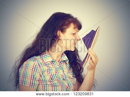 young woman sniffs smelly Slippers. On a gray background.