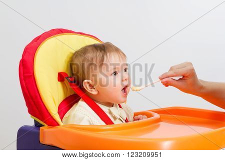 Baby boy eating with spoon at home in highchair