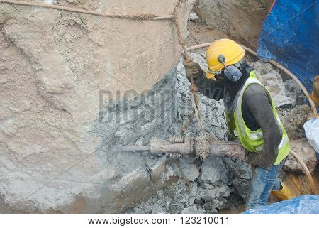 SELANGOR, MALAYSIA -AUGUST 08, 2015: A construction workers cutting foundation pile at the construction site. He using the heavy duty mobile hacker machine.