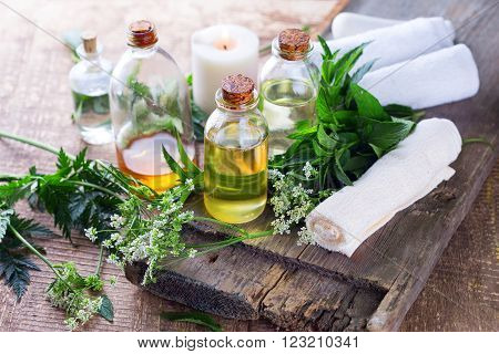 Organic essential aroma oil with herbs on aged wooden background. Homeopaty. Selective focus.