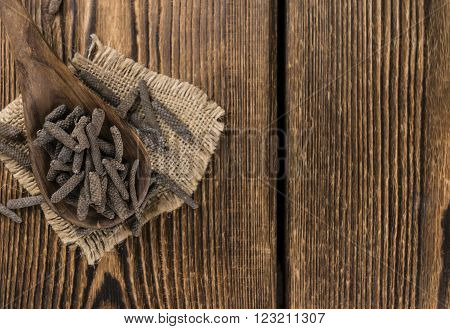 Dried Long Pepper (selective focus) on vintage wooden background