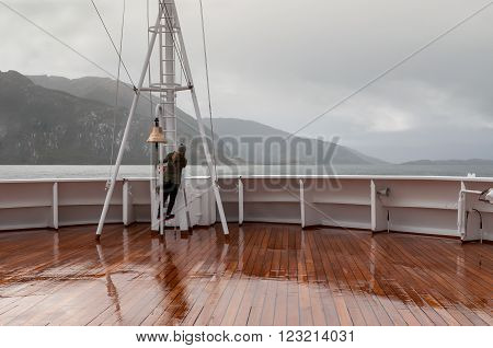 Beagle Channel, Chile - December 10, 2012: Passenger on board the cruise ship Veendam looking forward on the bow on Beagle Channel, Chile. Taken on a overcast rainy day. Sailing down the Beagle Channel in glacier alley and passing in front of these 5 glac