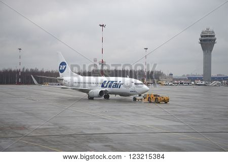 ST. PETERSBURG, RUSSIA - DECEMBER 12, 2015: Towing of aircraft Boeing 737-500 (VQ-BJQ) UTair aviation on the airfield. Pulkovo Airport