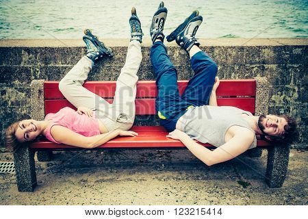 Young people friends in training suit with roller skates. Woman and man relaxing lying on bench outdoor.