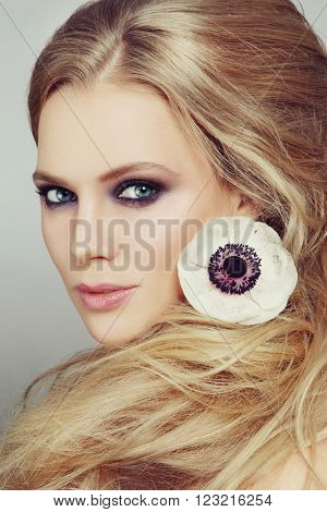 Close-up portrait of young beautiful woman with smoky eyes make-up and stylish messy hairdo