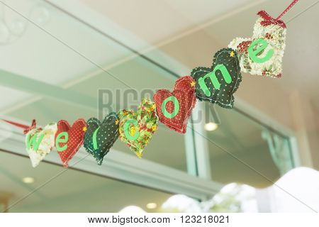 welcome message heart alphabet handmade hanging on mirror of decoration cafe coffee shop vintage style