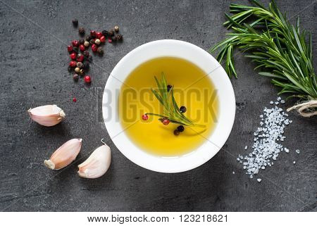 Black food background with olive oil fresh aromatic herbs and spices copy space top view.