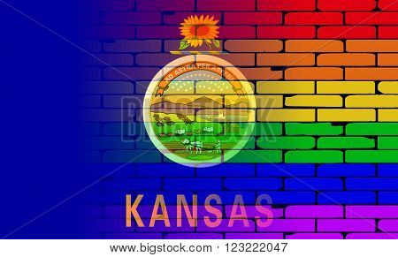 A well worn wall painted with a LGBT rainbow with the Kansas state flag
