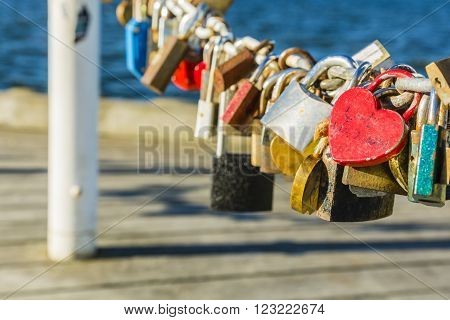 Red padlock heart stands out from other padlocks lovers.