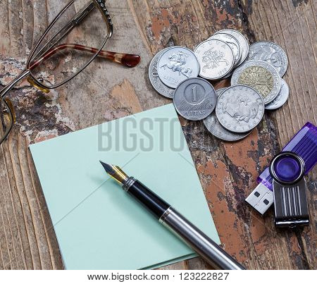 glasses pen and coins close-up business still life