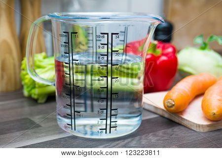 700ml / 7dl Of Water In A Measuring Cup On A Kitchen Counter With Vegetables