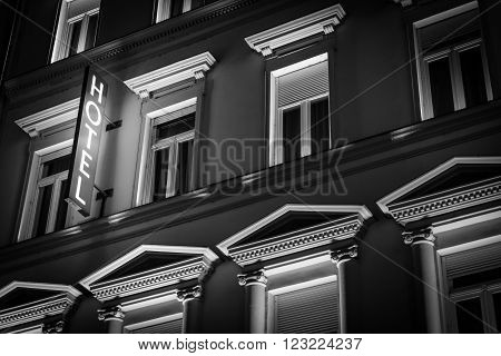 Glowing hotel sign in night on old building. Architecture of Budapest Hungary Europe travel.