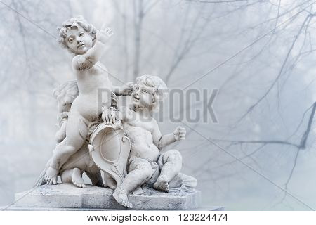 White statue of angel boys in park of city. Vienna Austria. Europe travel.