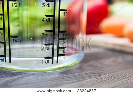 100ml / 1dl Of Water In A Measuring Cup On A Kitchen Counter With Vegetables