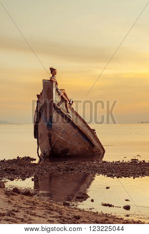Young woman is sitting on the shipwreck. Tropical sunset on the background.