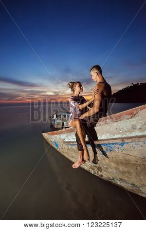Young couple is sitting on the sunken ship on the tropical sunset background.