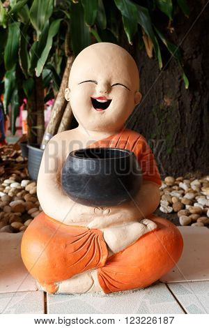 Statue of Novice Sculpture Young happy monk sitting