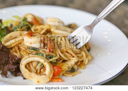stir-fried spicy spaghetti with seafood. thai style stir-fried spicy spaghetti with seafood. stir-fried spicy pasta with seafood.