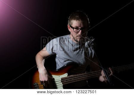 Playing rock guitarist surrounded with lights on dark background
