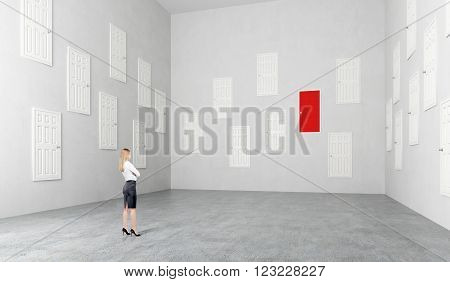 Businesswoman standing in room with many white doors one red Concept of choice.