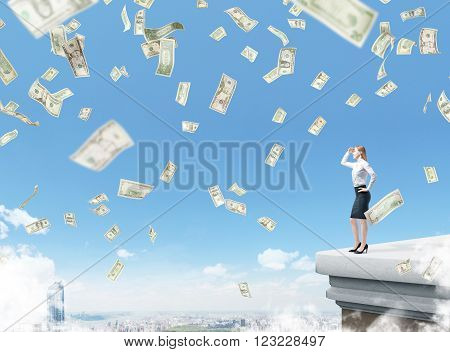 Businesswoman looking forward on roof dollars falling from above city view and blue sky. Concept of making money.