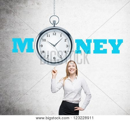 Businesswoman with finger up pocket watch over her. Concrete wall. Concept of time is money.