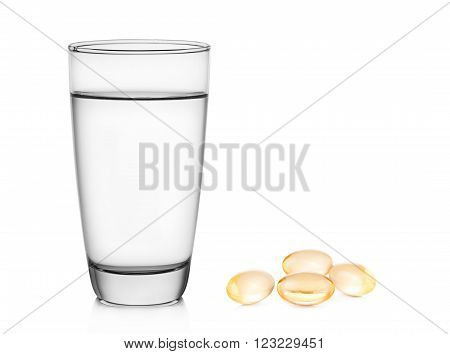 Glass of water and fish oil on white background