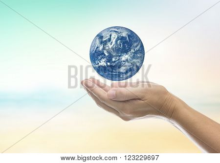 World on a human hand on a background blur sky with light and bokeh. - Concept help preserve the world together. Elements of this image furnished by NASA.