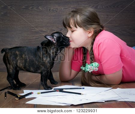Girl and dog. The girl's face and a large muzzle puppy. Dog French Bulldog. The relationship of the child and the dog. Concept - trust, love, the contents of dogs at home.