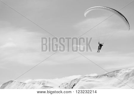 Paragliding in mountains in spring time. Blank space for a text. Black and white picture. Men on the right side. Georgia, Gudauri.