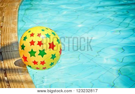 Retro look filter and selective focus / Inflatable ball floating in swimming pool, , With place for your text
