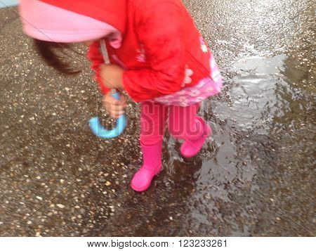 High angle view of toddler girl with umbrella outdoors at rainy day. Slow motion shot
