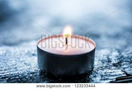 Romantic Winter Tea Light On Cracked Ice Above A Wooden Floorboard